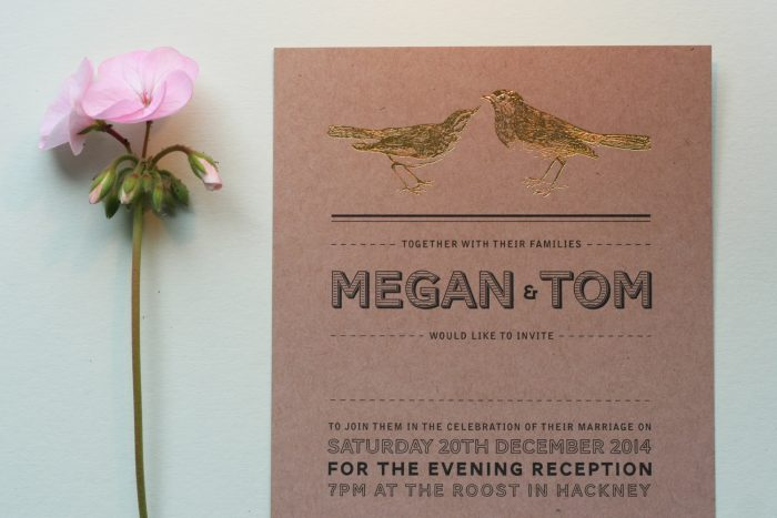 Engravers Wedding Invitation Foil Stamped in Gold on Kraft Card Next to a Flower