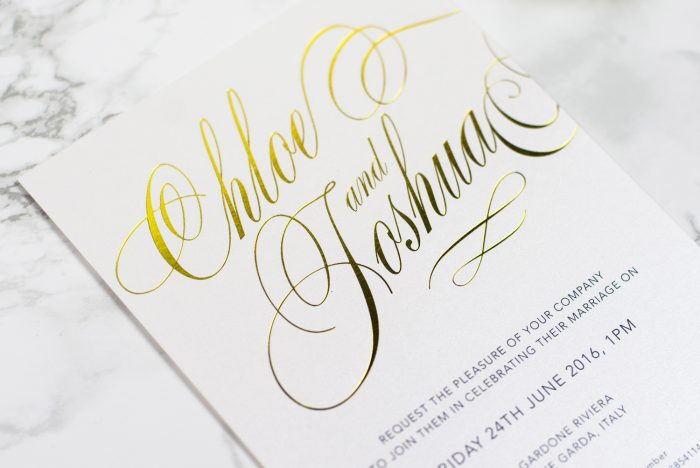 Script Wedding Invitation Foil Stamped in Gold on White Pearl Card Close Up